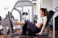 Woman working quads young her at machine press in the gym Royalty Free Stock Photography