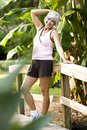 Woman in workout clothes standing park bridge Stock Photos