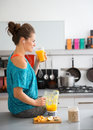 Woman in workout gear on kitchen counter drinking smoothie Royalty Free Stock Photo