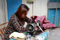 Woman works with a sewing machine by the road in amoy city china Royalty Free Stock Image