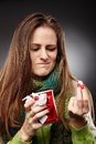 Woman wrapped up in a scarf and holding a cup of hot tea express closeup expressing disgust to some drugs she is over gray Stock Photos