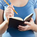 Woman writing in notebook casually dressed blue shirt with a pencil a small black Stock Image