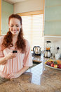 Woman writing text message in the kitchen Stock Image