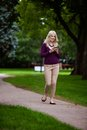 Woman writing text message in park looking at camera using cell phone Royalty Free Stock Image