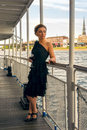 Woman on the yacht in black dress and glass of vine Royalty Free Stock Images
