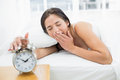 Woman yawning while extanding hand to alarm clock young extending in bed Royalty Free Stock Photography