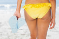Woman in yellow bikini standing back to camera holding flip flops on beach Royalty Free Stock Photos