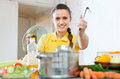 Woman in yellow cooking with ladle in saucepan beautiful at home Stock Photography