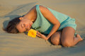 Woman with a yellow rose lies on the sand