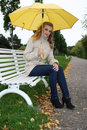 Woman with yellow umbrella sitting on bench Stock Image