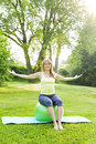 Woman on yoga balance ball female fitness instructor sitting exercise in green park Stock Images