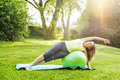 Woman on yoga balance ball female fitness instructor using exercise outdoors in morning sunshine Royalty Free Stock Image