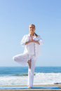 Woman yoga exercise gorgeous middle age doing at the beach Stock Photos
