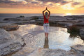 Woman yoga meditation by the ocean sunrise a standing at practicing pose rejuvenating soul quiet time and solitude in natures Stock Photography
