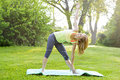Woman in yoga triangle pose female fitness instructor doing extended outdoors green park Stock Photo