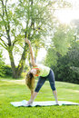 Woman in yoga triangle pose female fitness instructor doing extended outdoors green park Royalty Free Stock Image