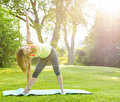 Woman in yoga triangle pose female fitness instructor doing extended outdoors morning sunshine Royalty Free Stock Photo