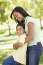 Woman and young boy outdoors embracing and smiling Stock Images