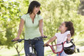 Woman and young girl on bikes outdoors smiling Royalty Free Stock Photo