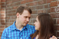 Woman and young man stand near brick wall Royalty Free Stock Photo