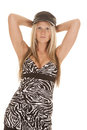 Woman zebra dress black hat hands up a in her print with her behind her head with a serious expression on her face Stock Image