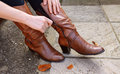 Woman zipping up high-heeled tan leather boots Royalty Free Stock Photo