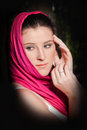 Womans face young adult female wearing a pink scarf over her head with a serene eastern look Stock Photos