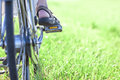 Womans foot on bicycle pedal on green grass closeup Royalty Free Stock Photo