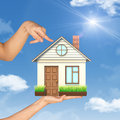 Womans hand fingering at house on palm blue sky background Royalty Free Stock Photos