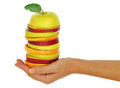 Womans hand with fresh fruit holding a stack of sliced Royalty Free Stock Photos