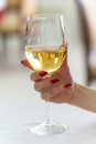 Womans hand holding wine glass of a young woman with red fingernails a of white Royalty Free Stock Images
