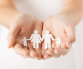 Womans hands with paper man family close up of cupped showing Royalty Free Stock Images