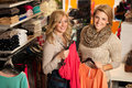 Womans shopping two girls in a clothes shop choo Stock Photography