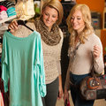 Womans shopping two girls in a clothes shop choosing garment Royalty Free Stock Photos