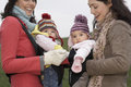 Women with babies in slings at park cheerful young mothers Royalty Free Stock Images