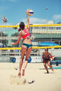 Women beach volleyball players. Woman jumping doing spike Royalty Free Stock Photo