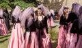 Women in beautiful Georgian dresses talking in crowd of people during popular wine festival