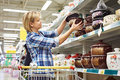 Women with cart shopping buys saucepan in supermarket Royalty Free Stock Photo