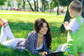 Women and child woman reading a book lying on the grass talk with the Royalty Free Stock Photography