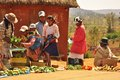 Women and children in the market in madagascar carrying on back selling vegetable on ground traditional Royalty Free Stock Images