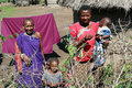 Maasai village, the African family standing near huts.