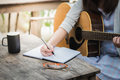 Women compose song and play guitar at the cafe Royalty Free Stock Images