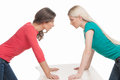 Women confrontation two angry looking at each other while holding their hands on the table Stock Photos