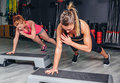 Women couple training over steppers in aerobic closeup of hard class on a fitness center sport and health concept Stock Image