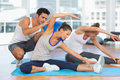Women doing stretching exercises as trainer helps one at fitness studio Stock Photo