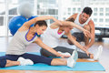 Women doing stretching exercises as trainer helps one at fitness studio Royalty Free Stock Images
