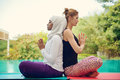 Women doing yoga by the poolside Royalty Free Stock Photo
