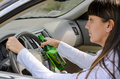 Women driver drinking and driving female while grinning out of the side window as she clutches the steering wheel with her bottle Royalty Free Stock Images