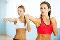 Women exercising two beautiful young in sports clothing and looking away Royalty Free Stock Photo