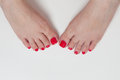 Women feet after pedicure with red nails on white background Stock Photos
